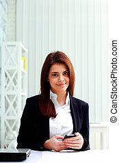 giovane, felice, donna d'affari, presa a terra, smartphone, su, lei, posto lavoro, in, ufficio