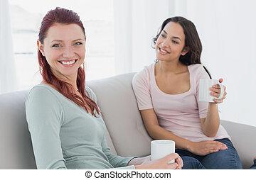 giovane, femmina, amici, con, tazze caffè, seduta, a casa