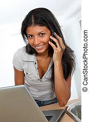 giovane, latino, donna usa laptop, computer, in, cucina casa