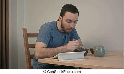 giovane, mangiare colazione, mentre, lettura, notizie, su, uno, tavoletta, computer