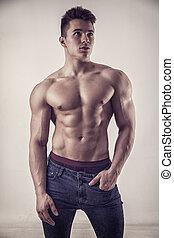 giovane, muscleman, standing, shirtless, su, sfondo scuro