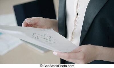 giovane, professionista femminile, è, dall'aspetto, documenti, standing, in, moderno, ufficio.