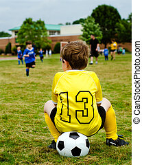 giovane ragazzo, bambino, in, uniforme, osservare, organizzato, gioventù, calcio, o, gioco football, da, sidelines