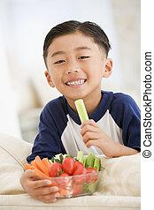giovane ragazzo, mangiare, ciotola vegetali, in, soggiorno, sorridente