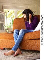 giovane, seduta, con, laptop, su, divano