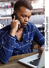 giovane, seduta, in, caffè, con, telefono mobile, guardando, laptop