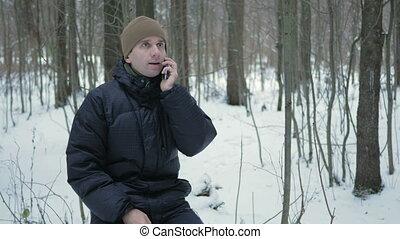 giovane, seduta, in, il, inverno, foresta, e, parlare, su, il, telefono., lui, ammira, il, lati, di, neve, e, alberi., uno, uomo, in, uno, scuro, giacca, e, uno, riscaldare, hat.