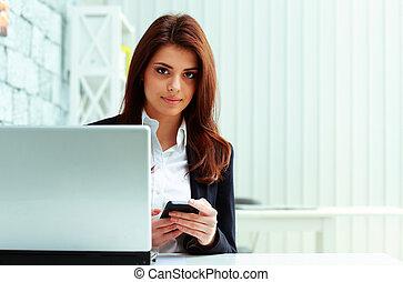 giovane, serio, donna d'affari, presa a terra, smartphone, su, lei, posto lavoro, in, ufficio