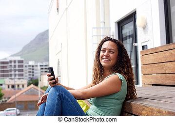 giovane, sorridente, con, telefono mobile, città