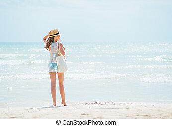 giovane, standing, su, spiaggia., vista posteriore