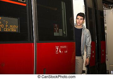 giovane, su, treno, standing, in, porta aperta, treshold