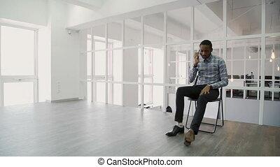 giovane, uomo affari, parlando telefono, mentre, seduta, in, moderno, ufficio.