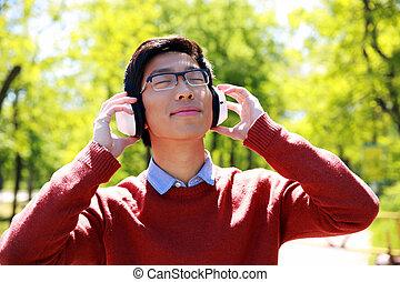 giovane, uomo asiatico, ascoltando musica, parco