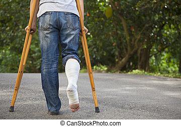 giovane, uomo asiatico, su, crutches, con, albero, fondo