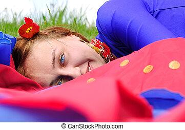 gipsy girl in blue, lying on green grass