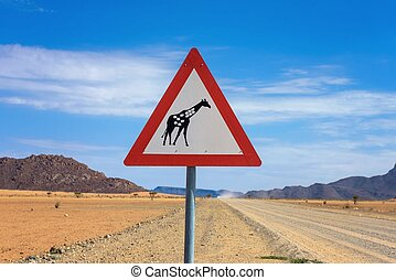 Giraffes crossing warning road sign placed in the desert of Namibia