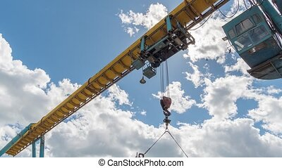 Girder gantry crane moves at construction site. Moving clouds.