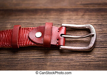 Girdle of red leather. Fashionable leather belt on a wooden ...