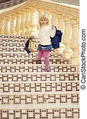 girl 3 years old comes down stairs with shopping