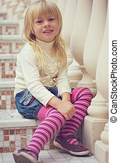 Girl 3 years old sitting on a beautiful staircase