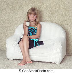 Girl 5 years old sitting on a sofa with cup