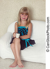 Girl 5 years old sitting on a sofa with cup - Girl 5 years...
