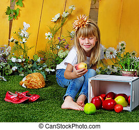 Girl 6 years old in garden with apples