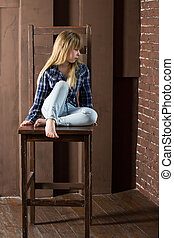 Girl 6 years old in jeans and a blue shirt is sitting on high chair