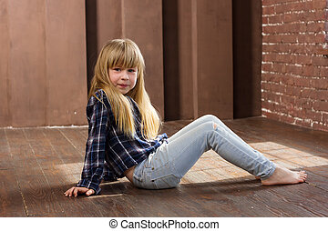 Girl 6 years old in jeans sitting on floor