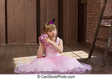 Girl 6 years old in pink dress with a piggy bank