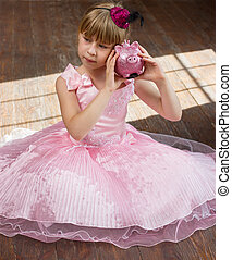Girl 6 years old in pink dress with a piggy bank square crop
