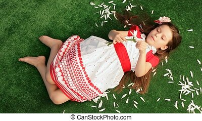 Girl 6 Years Old Lying on the Grass and Separates From the Chamomile Petals.