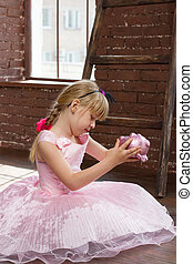 Girl 6 years old pink dress with piggy bank in his hands. Vertical framing