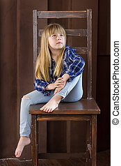 Girl 6 years old sitting on a high chair in room with brown walls