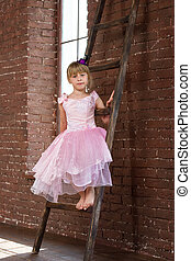Girl 6 years old sitting on the ladder