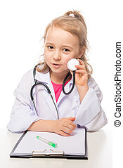 Girl 7 years with stethoscope in the doctor's suit playing, photo on the white background