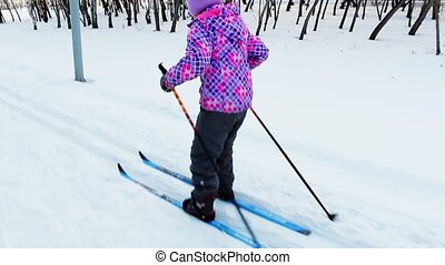 girl 8 years old in a bright pink jacket to learn to ski in...