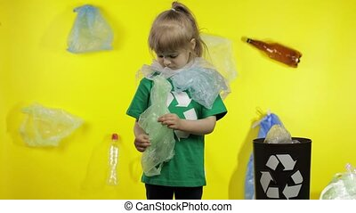 Child girl activist in t-shirt with recycle logo free up from plastic packages, put them in bin dump. Background with cellophane bags, bottles. Fight with plastic pollution. Think green. Save ecology