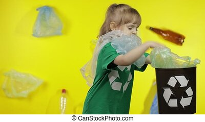 Child girl volunteer in green t-shirt with recycle logo free up from plastic packages and put them in bin dump. Background with cellophane bags, bottles. Fight with plastic pollution. Save ecology