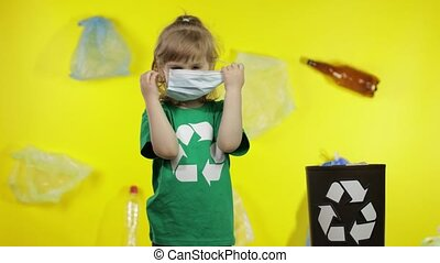Child girl activist in green t-shirt with recycle logo free up from medical mask, gloves and put them in bin dump. Fight with plastic pollution during coronavirus COVID-19 quarantine. Save ecology