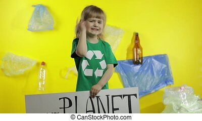Child girl activist in green t-shirt with recycle logo holding encouraging protesting poster Our Planet Needs Help. Background with cellophane bags, bottles. Save environment. Plastic nature pollution