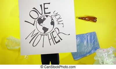 Girl activist holding poster Love Your Mother Earth. Plastic nature pollution