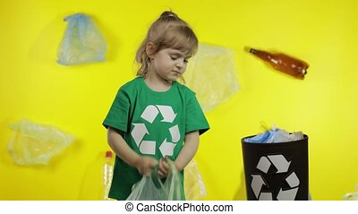 Child girl activist in green t-shirt with recycle logo in cellophane packages on her neck makes Earth globe free from plastic package. Yellow background. Reduce trash plastic pollution. Save ecology