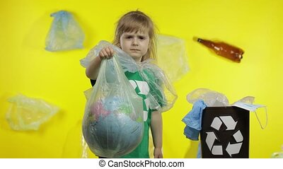 Child girl activist in green t-shirt with recycle logo in cellophane packages on her neck. Earth globe in plastic package. Background with bags, bottles. Reduce trash plastic pollution. Save ecology