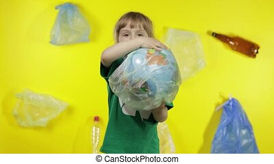 Child girl volunteer in green t-shirt with recycle logo makes Earth globe free from plastic package. Background with cellophane bags, bottles. Reduce trash contamination. Save ecology environment