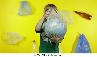 Child girl volunteer in t-shirt with recycle logo makes Earth globe free from plastic package. Background with cellophane bags bottles. Eliminate trash pollution. Think green. Save ecology environment