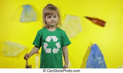 Child girl activist in t-shirt with recycle logo showing cellophane and paper packages. Background with cellophane bags, bottles. Eliminate plastic pollution. Think green. Save ecology environment