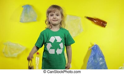 Junior girl activist in green t-shirt with recycle logo showing cellophane and paper packages. Background with cellophane bags, bottles. Reduce trash plastic contamination. Save ecology environment