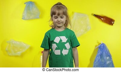 Junior girl activist in t-shirt with recycle logo showing cellophane and paper packages. Background with cellophane bags, bottles. Reduce trash plastic pollution. Ecology environment preservation