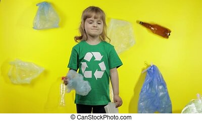 Child girl activist in green t-shirt with recycle logo showing cellophane and paper packages. Background with cellophane bags, bottles. Eliminate trash plastic contamination. Save ecology environment